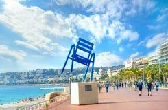Scène de rue avec la sculpture en art contemporain de la chaise bleue sur Promenade des Anglais à Nice france images libres de droits