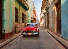 Scène de rue avec une vieille voiture américaine rouillée Images stock