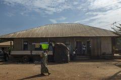 Scène de rue dans les périphéries de la ville du Bissau avec de l'eau de transport femme dans le seau sur sa tête, en Guinée-Biss image stock