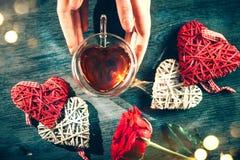 Scène de Saint-Valentin de St Les mains de la femme tenant la tasse de thé en forme de coeur avec le décor rouge de coeurs de rot photo libre de droits