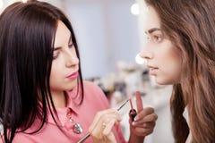 Scène des coulisses : Artiste de maquillage professionnel faisant le maquillage pour le yo Image libre de droits