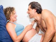 Scène drôle et tendre de papa écoutant heureusement son wif enceinte Photographie stock libre de droits