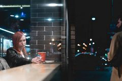 Scène dramatique, fille travaillant sur l'ordinateur portable en café, smartphone de prise dans des mains, stylo, téléphone d'uti images libres de droits