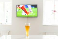 Scène du football à la télévision et à un verre de bière de blé sur une table Photographie stock