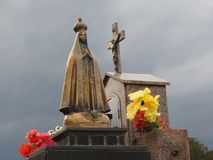 Scène in een begraafplaats: graf met het standbeeld van Onze Dame en een kruisbeeld stock fotografie