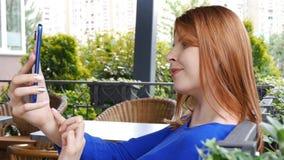 Scène en gros plan d'une fille avec du charme avec les cheveux rouges qui font un selfie dans le café confortable La fille sourit clips vidéos