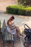 Scène extérieure avec allaiter la maman s'inquiétant le petit nourrisson dans des ses bras, se reposant sur le banc, après le pro photos stock