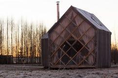 Scène hivernale dramatique avec la maison en bois et le lever de soleil rose photos stock