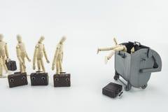 Scène métaphorique, cadres jetant dans une poubelle, poupées en bois d'isolement sur le fond blanc photo stock