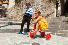 Scène met kinderen het spelen, cop en bestuurder in openlucht Stock Fotografie