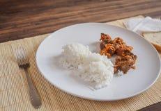 Scène met sneeuw witte ceramische schotel van rijst en braadstukvlees, hutspot, vlees met groenten op een bamboeservet op houten Stock Foto