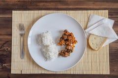 Scène met sneeuw witte ceramische schotel van rijst en braadstukvlees, hutspot, vlees met groenten op een bamboeservet op houten Royalty-vrije Stock Foto's