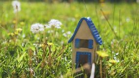Scène met stuk speelgoed huis in het gras die eco-huis vertegenwoordigen stock video