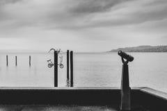 Scène minimaliste noire et blanche d'un port avec une visionneuse à jetons et de plusieurs piliers avec une bicyclette dans un po photo libre de droits