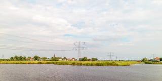 Scène néerlandaise rurale avec un petit village et des pylônes de l'électricité Photo stock