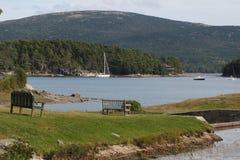 Scène paisible de montagne avec le lac, bateaux, banc, herbe Photo libre de droits
