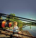 Scène pittoresque de la pêche mignonne de petit garçon du dock en bois Photos stock