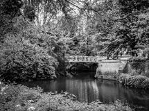 Scène tranquille montrant un petit pont décoratif en fer traversant une rivière immobile à une île privée photographie stock