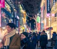 Scène urbaine avec des personnes de foule à la rue d'achats la nuit dedans Images stock