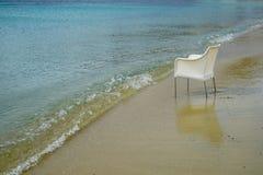 Scène van lege stoel in witte rotanzitting op zandstrand met zachte golf, schaduwen van blauwe en duidelijke zeewaterachtergrond Royalty-vrije Stock Afbeelding