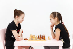 Scacchi del gioco di due ragazze su fondo bianco Immagine Stock Libera da Diritti