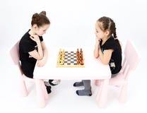 Scacchi del gioco di due ragazze su fondo bianco Fotografie Stock