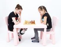 Scacchi del gioco di due ragazze su fondo bianco Immagini Stock