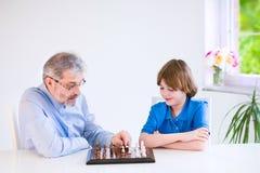 Scacchi di gioco di prima generazione felici con il suo nipote Fotografie Stock Libere da Diritti