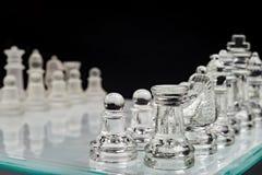 Scacchi, scacchiera di vetro con i pegni su un fondo nero immagini stock libere da diritti