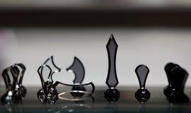 Scacchiera con i pezzi degli scacchi su fondo grigio Fotografia Stock