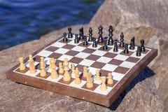 Scacchiera con i pezzi degli scacchi su roccia con la parte posteriore dell'argine del fiume Fotografie Stock Libere da Diritti