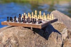 Scacchiera con i pezzi degli scacchi su roccia con la parte posteriore dell'argine del fiume Fotografie Stock