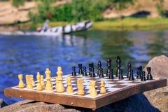 Scacchiera con i pezzi degli scacchi su roccia con la parte posteriore dell'argine del fiume Fotografia Stock