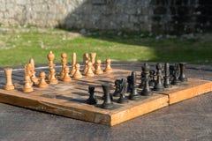Scacchiera di legno antica su una tavola di legno all'aperto, attività strategica all'aperto Immagine Stock
