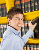 Scaffale bello di Choosing Book From dello studente dentro Fotografia Stock Libera da Diritti