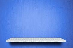 Scaffale bianco sul fondo blu del cemento per l'esposizione del prodotto immagine stock libera da diritti