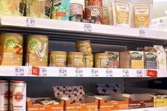 Scaffale con gli integratori alimentari sani come le scosse delle polveri e della proteina della frutta nella catena tedesca dell fotografia stock