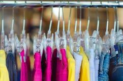 Scaffale con i vestiti della femmina della donna dei ganci Immagine Stock