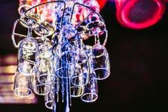 Scaffale con i vetri puliti vuoti nella barra di notte fotografie stock