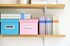 Scaffale con le scatole e l'album di foto immagini stock libere da diritti