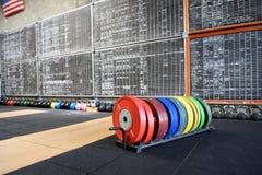 Scaffale dei pesi di formazione variopinti in una palestra Immagine Stock