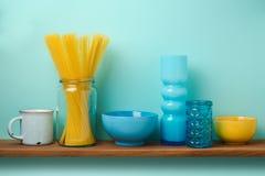 Scaffale della cucina con pasta e piatti sopra retro fondo blu Immagine Stock
