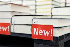 Scaffale della libreria con il mucchio dei nuovi libri con il piatto rosso Nuovi arrivi alla libreria Presentazione del libro immagini stock libere da diritti