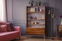 Scaffale di legno rinnovato con il modello geometrico e un ottone f fotografie stock