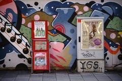 Scaffale di rivista e scatola di distribuzione elettrica davanti alla parete dei graffiti Fotografie Stock