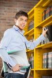 Scaffale di Selecting Book From dello studente maschio in biblioteca Fotografia Stock