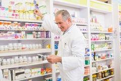 Scaffale di Taking Medicine From del farmacista Fotografia Stock