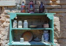 Scaffale dipinto che contiene i barattoli di vetro, le ciotole, i piatti ed altri oggetti fotografia stock libera da diritti