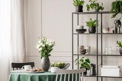 Scaffale industriale del metallo con i piatti e le piante nella sala da pranzo luminosa con la tavola rotonda con le sedie fotografia stock libera da diritti