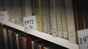 Scaffale per libri con gli archivi Vecchi libri storici multicolori in biblioteca stock footage